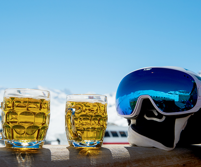 Steins of beer next to a ski helmet and goggles