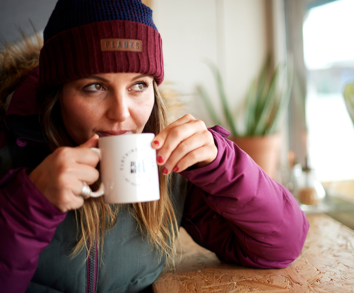 Girl drinking hot drink in a ski resort