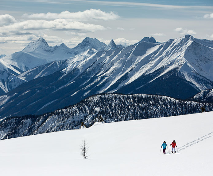 Skiing couple walking on mountain in Banff, Canada with views of the Canadian Rockies. Crystal Ski Holidays