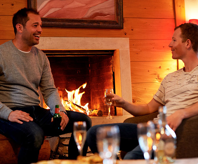Two men with drinks by the fireplace. Crystal Ski Holidays