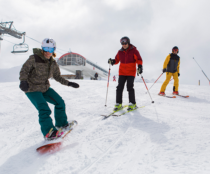 Snowboarder and skiers