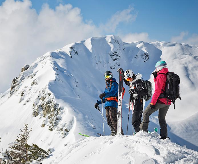 Three skiers on a mountain peak