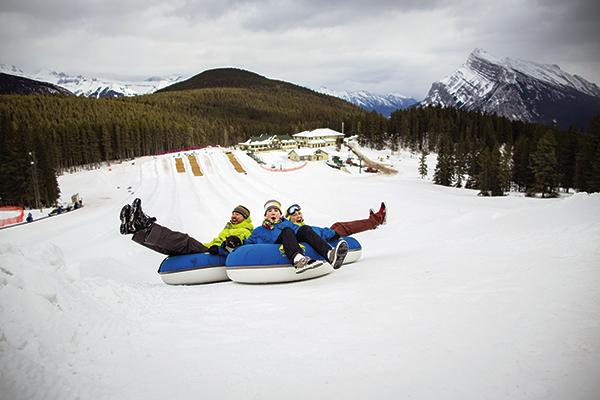 Three people snow tubing.