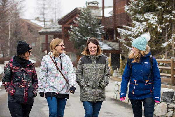 Four women walking down a street.