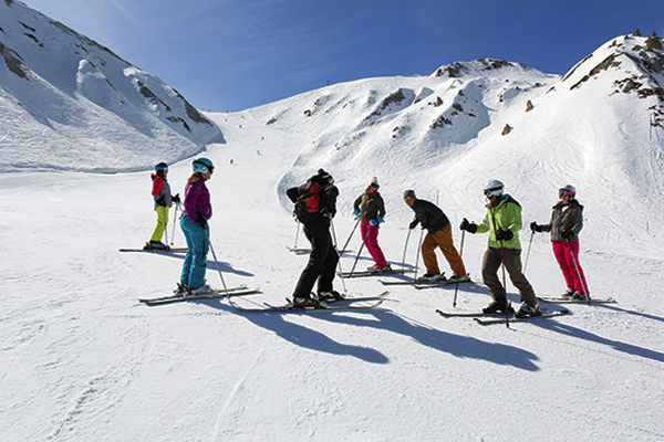 Group of skiers standing on a ski slope.