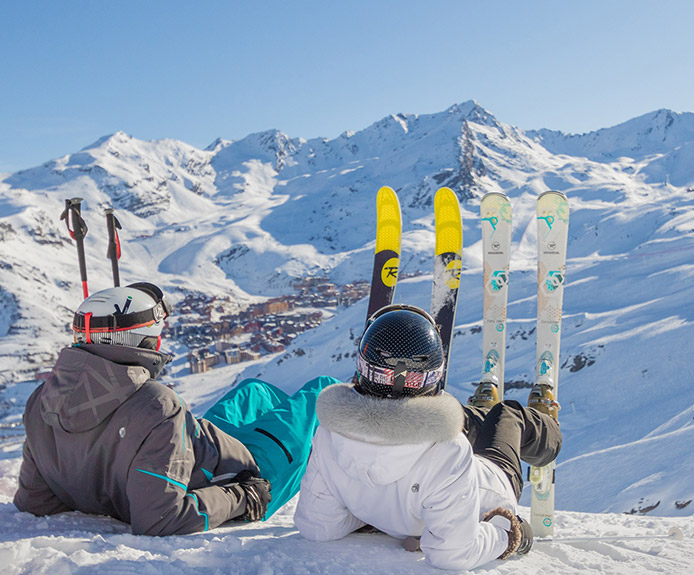 Skiers sitting on snow in Val Thorens