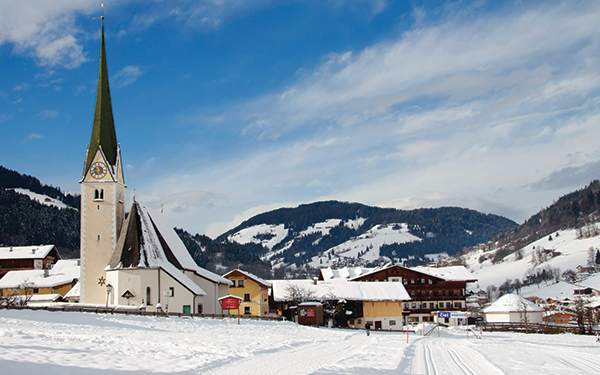 snow covered village with a church