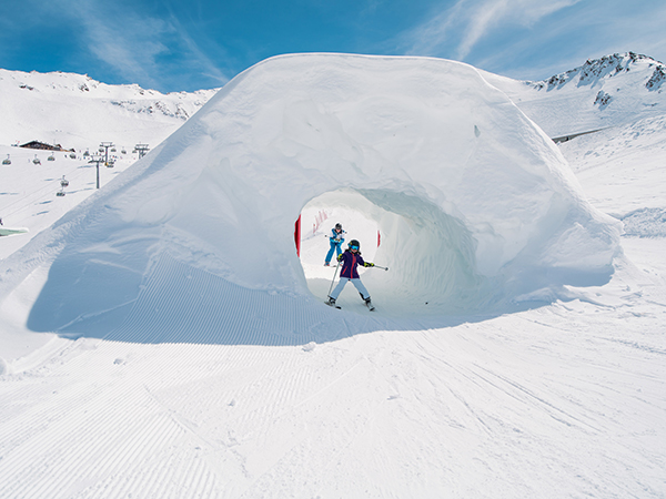 child skiing through snow tunnel